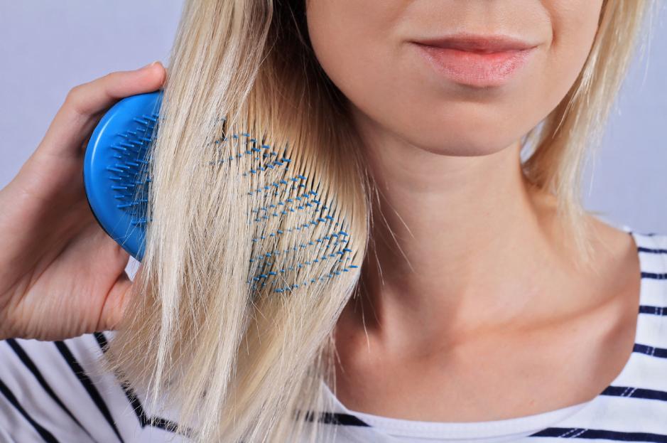 woman brushing thin hair maxim hair restoration
